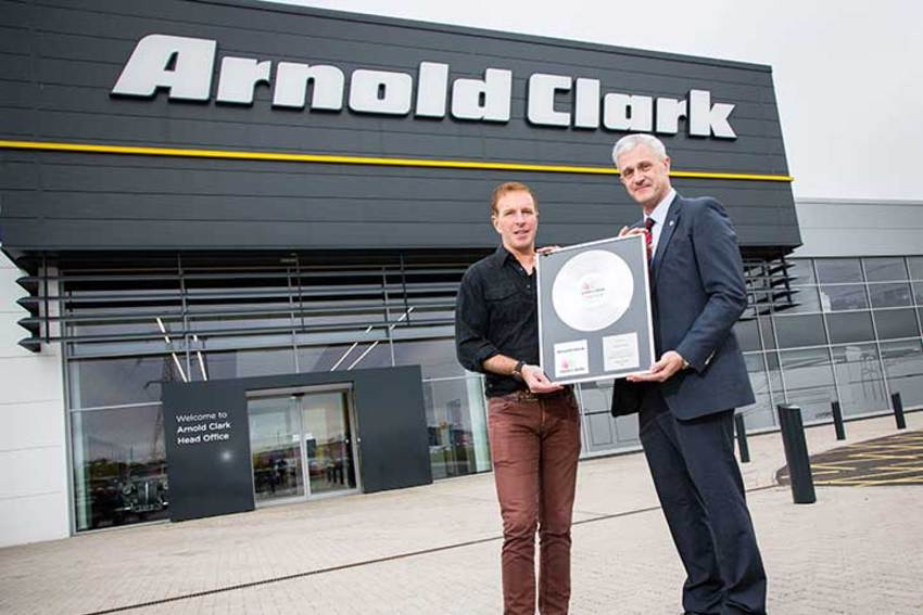 George Bowie presenting the award to Group Managing Director, Eddie Hawthorne at Arnold Clark HQ, Hillington.